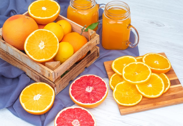Oranges and lemons in the wooden box in front of glasses of orange juice on violet cloth