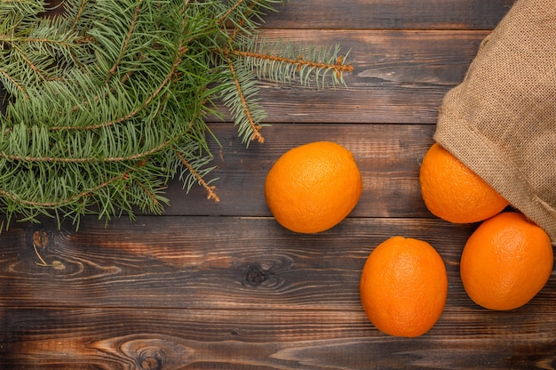 Oranges in a linen bag on a wooden surface near fir branches top view