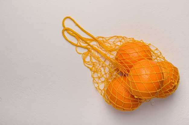 Oranges in a mesh string bag made of natural material on light surface