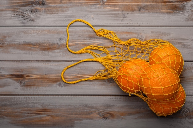 Oranges in a mesh string bag made of natural material on wood surface