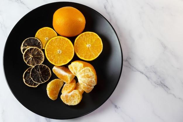 Апельсины на вид сверху черной тарелке