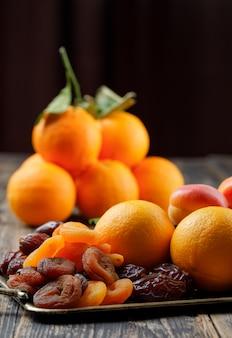 Апельсины на ветке с датами, сушеные и спелые абрикосы в лоток вид сбоку на деревянный стол