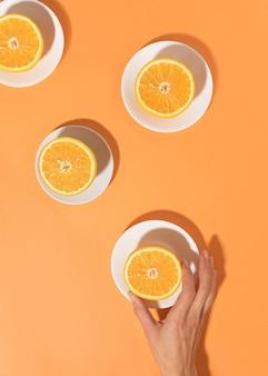 明るいテーブルと女性の手の上のプレートにオレンジ。最小限の食品の概念。フラットレイ。