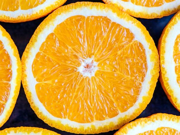 Апельсины или грейпфруты разрезают пополам на черном фоне. крупным планом макрос