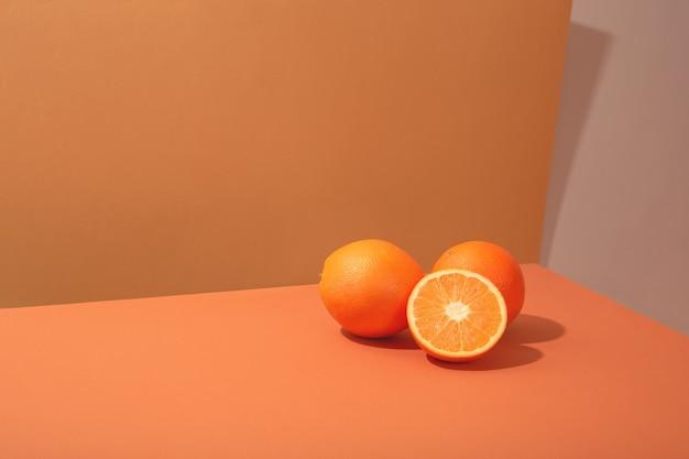 生姜のテーブルにオレンジが散らばっています。ジューシーな柑橘系の果物と概念的なミニマルな夏の静物。ハードライト。