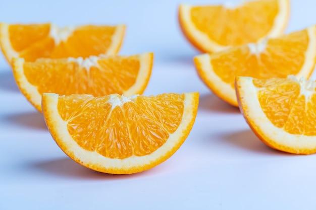 Ломтик апельсина на белой поверхности.