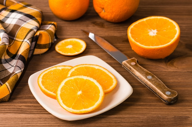 Oranges sliced and whole, knife and napkin on a wooden background