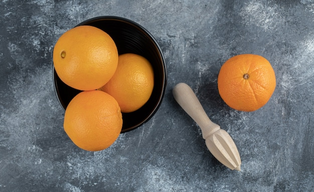 Oranges and squeezing tool on marble table.