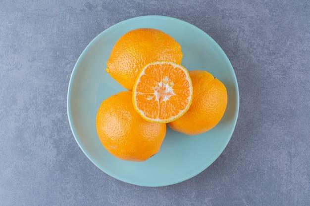 Апельсины сложены друг на друга на мраморном столе.