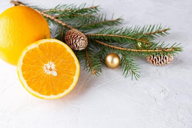 밝은 배경에 크리스마스 공과 콘이 있는 가문비나무 가지가 있는 오렌지 크리스마스 및 새