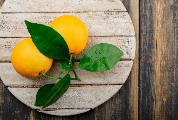 Апельсины с веткой на деревянной и разделочной доске