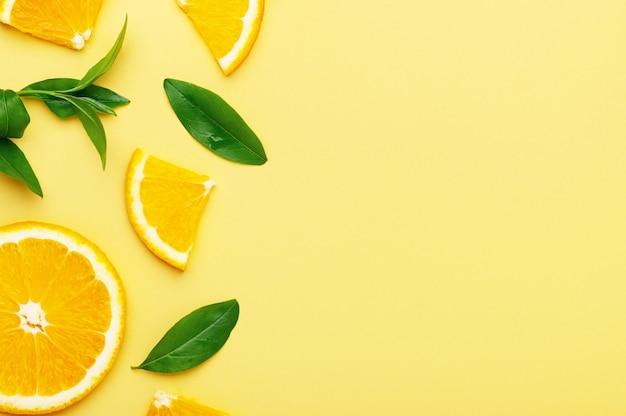 Апельсины с дольками и кусочками с листьями на желтом фоне. сочные цитрусовые органические летние фрукты с витамином с плоской планировкой, копией пространства.