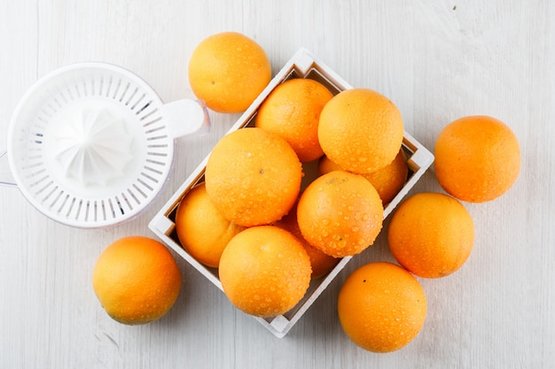 Oranges with squeezer in a wooden box on wooden surface, flat lay.