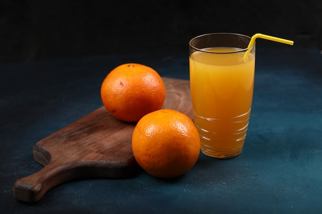 Oranges on a wooden board with a glass of juice. black background.