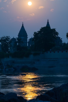 Orchha cityscape from the river at sunset, temple silhouette. india.