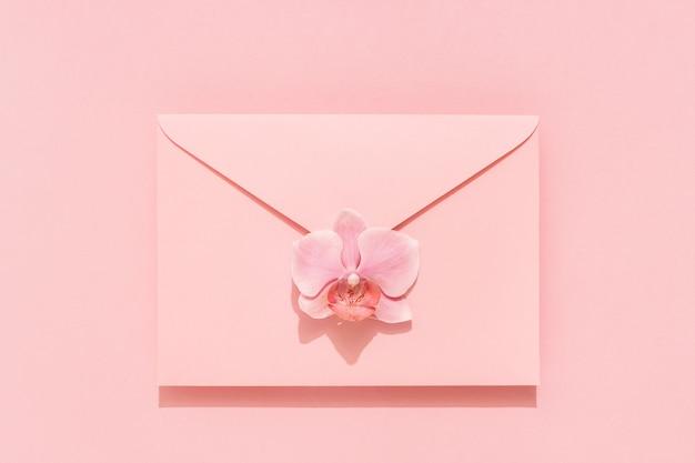 ピンクの封筒に蘭の花。女性、母の日、バレンタイン、誕生日おめでとうカード。フラットレイ、休日の背景。