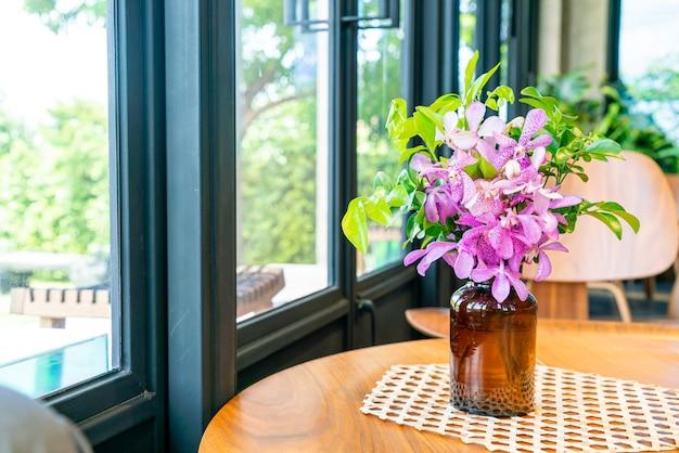 コーヒーショップカフェレストランのテーブルの上に花瓶の装飾の蘭の花