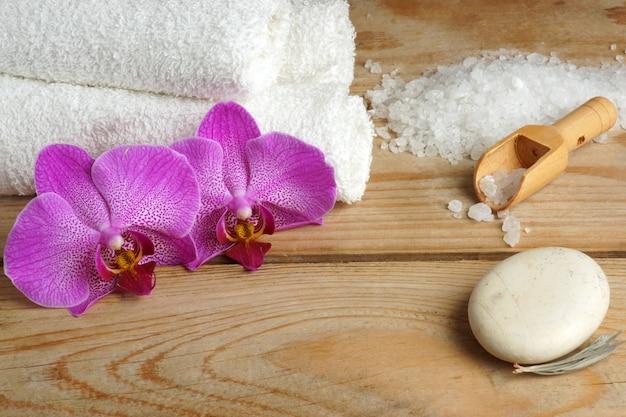 白い海の塩と木製の背景に蘭の花