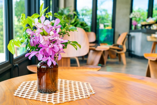 Orchid flowers in vase decoration on table in coffee shop cafe restaurant