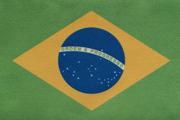 Государственный герб федеративной республики бразилия. флаг бразилии на близком расстоянии. ordem e progresso