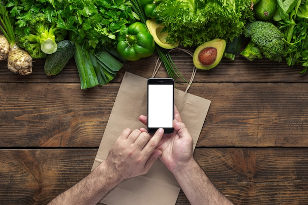 Order food online man holds smartphone with blank screen on wooden table with fresh green vegetables