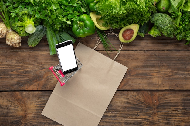 Order food online phone in shopping cart on wooden table with clean green vegetables and paper bag top view