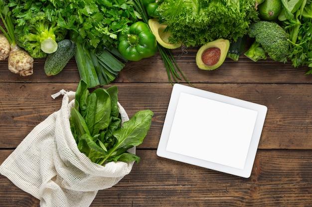 新鮮な緑の野菜とファブリックバッグの木製テーブルに空白の画面を持つ食品オンラインタブレットを注文します。