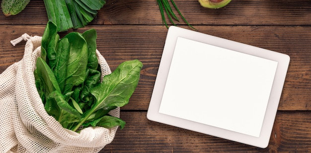 Order food online tablet with blank screen on wooden background with fresh green vegetables and fabric bag