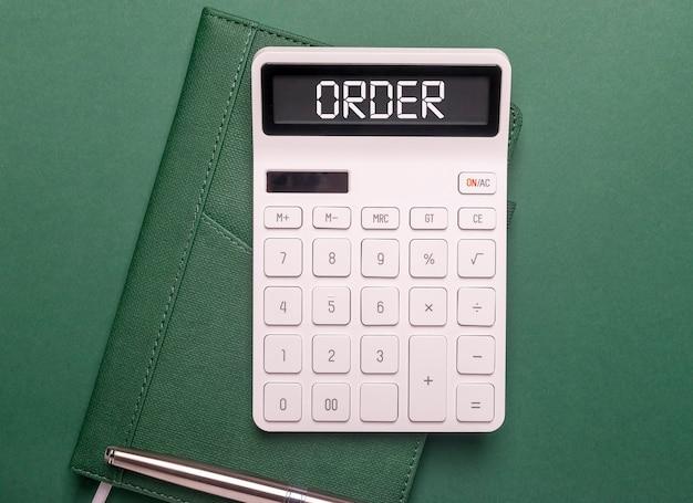 緑のテーブルの電卓の単語、碑文を注文します。