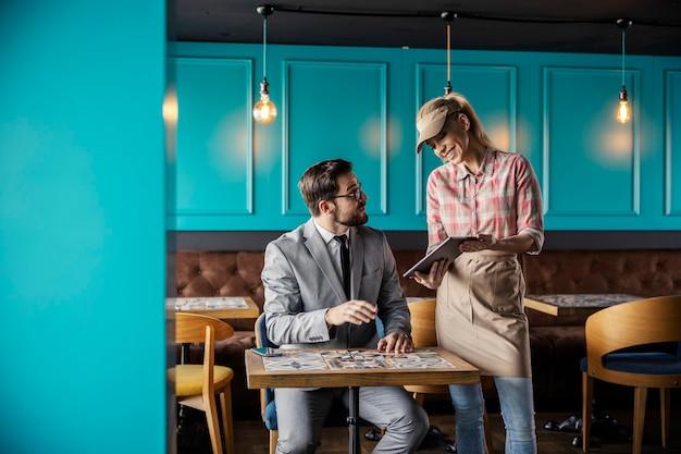 レストランで食べ物や飲み物を注文する。ビジネススーツを着た男性客がレストランのテーブルに座ってウェイトレスに助けを求めている。彼女はデジタルタブレットを持って、彼にメニューを見せます