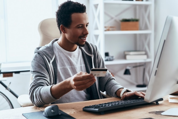 Ordering something. happy young man in casual clothing making a purchase online while spending time at home