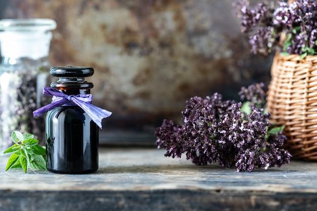 木製の背景にガラス瓶の中のオレガノのエッセンシャルオイル。コピースペース