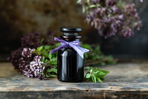 Эфирное масло орегано в стеклянной бутылке на деревянных фоне. копировать пространство