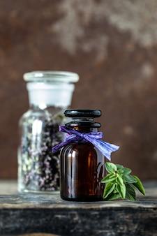 木製の背景にガラス瓶のオレガノエッセンシャルオイル。コピースペース