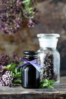 Эфирное масло орегано в стеклянной бутылке на деревянной поверхности