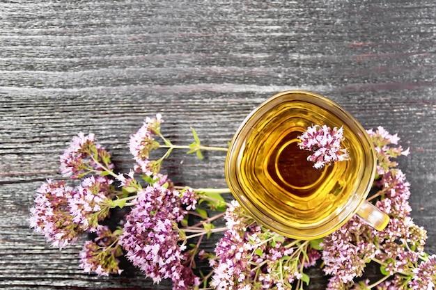 ガラスカップのオレガノハーブティー、上から木の板の背景に新鮮なピンクのマジョラムの花