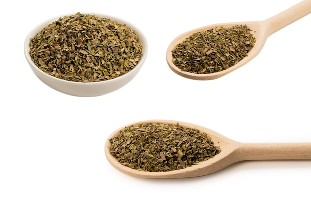 Oregano spice in wooden spoon isolated on white surface