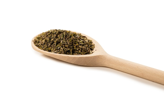 Oregano spice in wooden spoon isolated on white