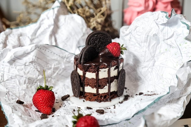 Oreo cake with oreo cookies strawberry chocolate syrop side view