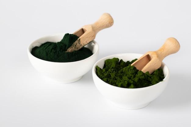 흰색 배경에 나무 국자가 있는 흰색 그릇에 분말 형태의 유기농 조류 클로렐라와 스피루리나.
