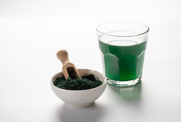 木製のスクープと白い背景の上の透明なガラスに溶解したスピルリナ粉末と粉末の有機藻スピルリナ。