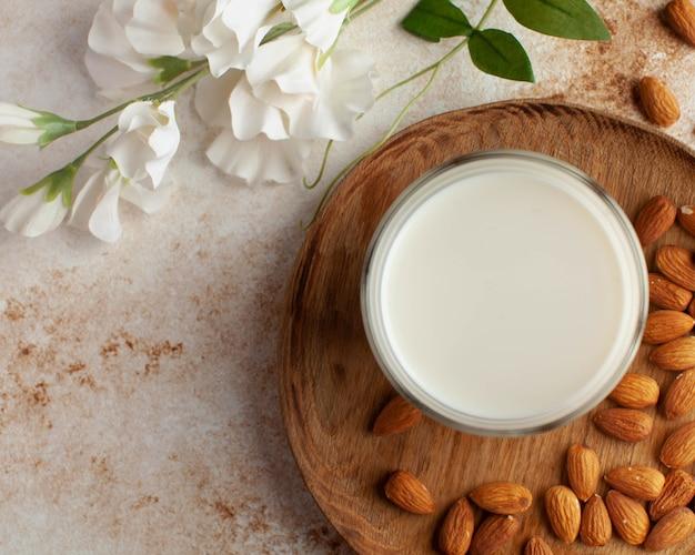 채식주의자를 위한 유제품 우유에 대한 갈색 배경의 유기농 아몬드 우유 아몬드...