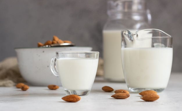 Organic almond milk in glass jugs with ingredients