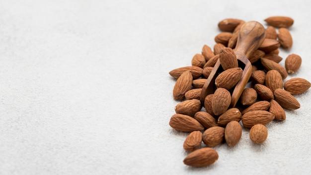 Органические миндальные орехи и деревянная ложка для копирования