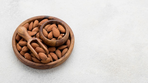 Organic almond nuts in bowl copy space