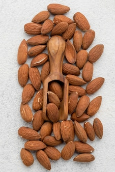 Organic almond nuts and wooden spoon  flat lay
