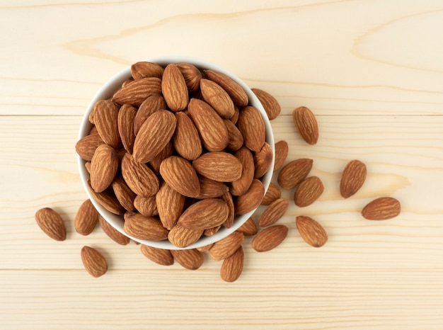 Organic almonds in ceramic bowl and heap almonds top view on wooden
