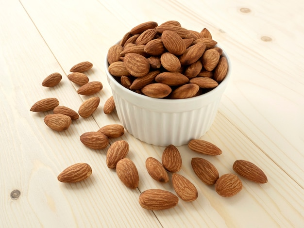 Organic almonds in ceramic bowl and heap almonds on wooden