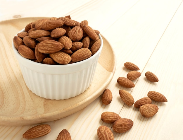 Organic almonds in ceramic bowl with wooden tray and heap almonds on wooden