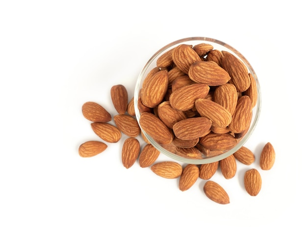Organic almonds in glass bowl and heap almonds isolated top view on white